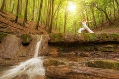 La relaxation, femme pratique le yoga à la cascade image stock
