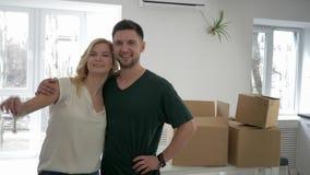 La relocalización en el hogar alquilado, retrato de los nuevos dueños del apartamento de los recienes casados muestra llaves al p almacen de video