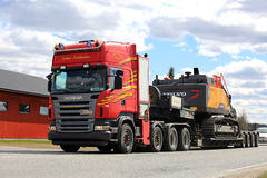 La remorque rouge de Scania semi transporte l'excavatrice hydraulique Photo stock
