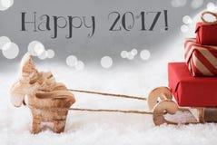 La renna con la slitta, fondo d'argento, manda un sms a 2017 felice Immagine Stock