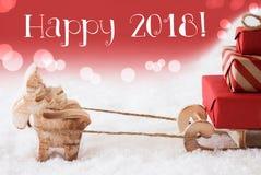 La renna con la slitta, fondo rosso, manda un sms a 2018 felice Fotografia Stock