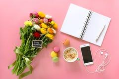 La renoncule de fête de concept de matin fleurit avec bonjour note, tasse de cappuccino, makaron de gâteau, mobile avec des écout Photos stock