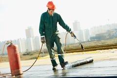 La reparación de la cubierta de tejado plano trabaja con fieltro de la techumbre Imagen de archivo libre de regalías