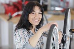 La reparaci?n femenina madura del mec?nico de la bicicleta rueda en taller fotos de archivo libres de regalías