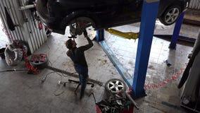 La reparación masculina del mecánico levantó para arriba el automóvil en el taller de reparaciones del coche metrajes
