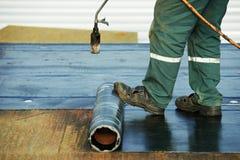 La reparación de la cubierta de tejado plano trabaja con fieltro de la techumbre Foto de archivo libre de regalías