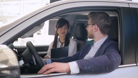 La representación auto, encargado de ventas de sexo femenino asiático amistoso del coche aconseja al comprador de sexo masculino  almacen de video