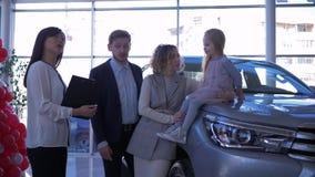 La representación auto, familia joven de los compradores con la muchacha del niño comunica con el encargado del coche sobre el nu almacen de video