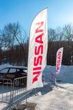 La representación señala Nissan por medio de una bandera sobre el cielo azul en día soleado Nissan es a Fotografía de archivo