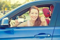 La représentation heureuse de conducteur de femme manie maladroitement vers le haut de sortir de la fenêtre de voiture Photographie stock