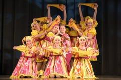 La représentation théâtrale des enfants du groupe de danse dans des costumes nationaux Photo stock