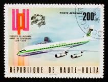 La Repubblica del francobollo di Alto Volta mostra l'emblema e l'aeroplano dell'UPU, circa 1974 Fotografie Stock Libere da Diritti