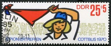 LA REPUBBLICA DEMOCRATICA TEDESCA - 1970: attività della ragazza di manifestazioni della bandana pionieristica della tenuta e di  Fotografia Stock Libera da Diritti