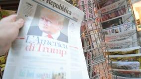 La republica Magazine about Donald Trump new USA president. PARIS, FRANCE - NOV 10, 2016: Man buying Italian newspaper La Republica with shocking headline title stock video footage