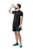La resistenza esaurita stanca della tenuta dell'istruttore di forma fisica lega il frullato bevente Immagini Stock