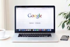 La retina de MacBook Pro con el Home Page de Google en la pantalla se coloca encendido Foto de archivo