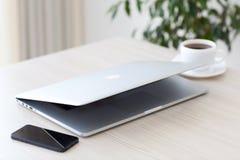 La retina di MacBook Pro del computer portatile e il iPhone 5s sta trovandosi sulla Tabella I Immagine Stock