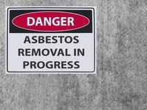 La retirada de amianto del peligro de la muestra de la etiqueta engomada en la pared del amianto del yeso imagen de archivo