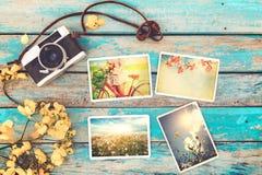 La retro macchina fotografica e l'album di foto di carta istantaneo sulla tavola di legno con il confine dei fiori progettano Fotografia Stock Libera da Diritti