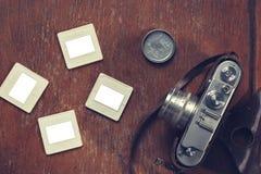 La retro macchina fotografica ed i vecchi scorrevoli mettono su una sedia fotografie stock