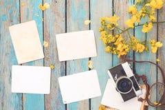 La retro macchina fotografica ed il vecchio album di foto di carta istantaneo vuoto sulla tavola di legno con il confine dei fior Fotografie Stock Libere da Diritti