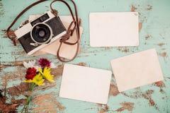 La retro macchina fotografica ed il vecchio album di foto di carta istantaneo vuoto sulla tavola di legno con il confine dei fior Fotografia Stock Libera da Diritti