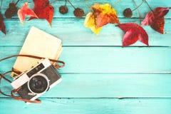 La retro macchina fotografica ed il vecchio album di foto di carta istantaneo vuoto sulla tavola di legno con le foglie di acero  Immagine Stock