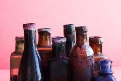 La retro progettazione imbottiglia la macro vista Insieme di vetro sporco variopinto del flacon Fondo rosa, profondità di campo b Fotografie Stock Libere da Diritti