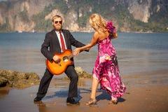 La retro-vista bionda evita il gioco della chitarra Fotografia Stock