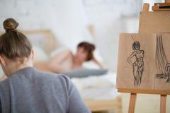 La retrovisione del pittore femminile disegna gli schizzi della donna nuda nella classe di disegno Fotografia Stock Libera da Diritti