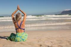 La retrovisione della donna con le armi ha sollevato l'yoga di pratica mentre si sedeva sulla riva Fotografie Stock