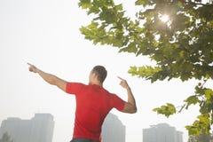 La retrovisione di giovane uomo muscolare che allunga da un albero, arma alzato e dita che indicano verso il cielo a Pechino, Cina Fotografia Stock