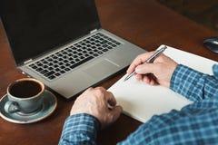 La retrovisione ha sparato di scrittura occupata dell'uomo di affari delle mani dalla penna e computer portatile usando alla scri Fotografia Stock