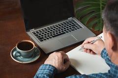 La retrovisione ha sparato di scrittura occupata dell'uomo di affari delle mani dalla penna e computer portatile usando alla scri Fotografia Stock Libera da Diritti