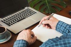 La retrovisione ha sparato di scrittura occupata dell'uomo di affari delle mani dalla penna in taccuino e computer portatile usan Fotografia Stock Libera da Diritti