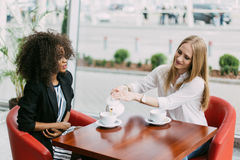 La reunión de dos mujeres hermosas El afroamericano está hablando mientras que el bolnde uno está vertiendo el té en el café Imagenes de archivo
