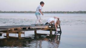 La ricreazione all'aperto, i bambini svegli ragazzo e la ragazza sul ponte di legno stanno lasciando sulle barche di carta del fi stock footage