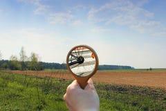 La riflessione della bici nello specchio sui precedenti del campo fotografia stock