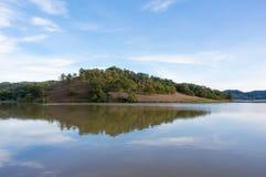 La riflessione della collina del pino sul lago con cielo blu e le nuvole alla mattina fotografia stock