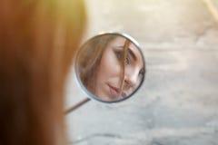 La riflessione di bella ragazza in un motociclo ha stato abbattuto il retrovisore MI Fotografia Stock