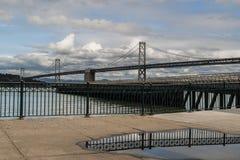La riflessione di Bridgesdella baia di Oakland - di San Francisco in una pozza Fotografia Stock Libera da Diritti