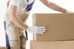 La rilocazione assiste il concetto Motore in uniforme con i cardboardboxes isolati su fondo bianco fotografia stock libera da diritti