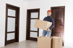 La rilocazione fornisce un servizio all'uomo con i cardboardboxes Lavoratore che trasporta le cose nell'appartamento Muovendosi v fotografie stock