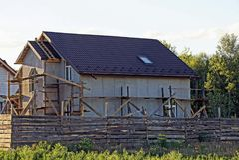 La riparazione di una casa grigia sotto le mattonelle dietro un di legno recinta l'erba Immagine Stock Libera da Diritti