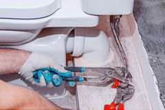 La riparazione residenziale, sostituisce la valvola della valvola, scandagliante il primo piano, pinze rosse dell'impianto idraul immagine stock