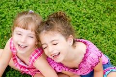 La risa de las muchachas de los niños se sienta en hierba verde Fotos de archivo
