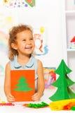 La risa mirando a la muchacha sostiene la tarjeta con el árbol de Navidad Imágenes de archivo libres de regalías