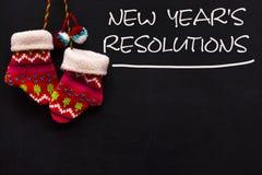 La risoluzione del nuovo anno di parola scritta sulla lavagna con guanti fotografie stock