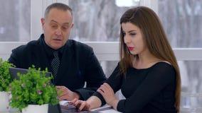 La riunione d'affari, ragazza attraente con l'anziano discute i dettagli del contratto con il computer portatile