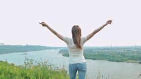 La riuscita donna che solleva le mani si avvicina al fiume archivi video